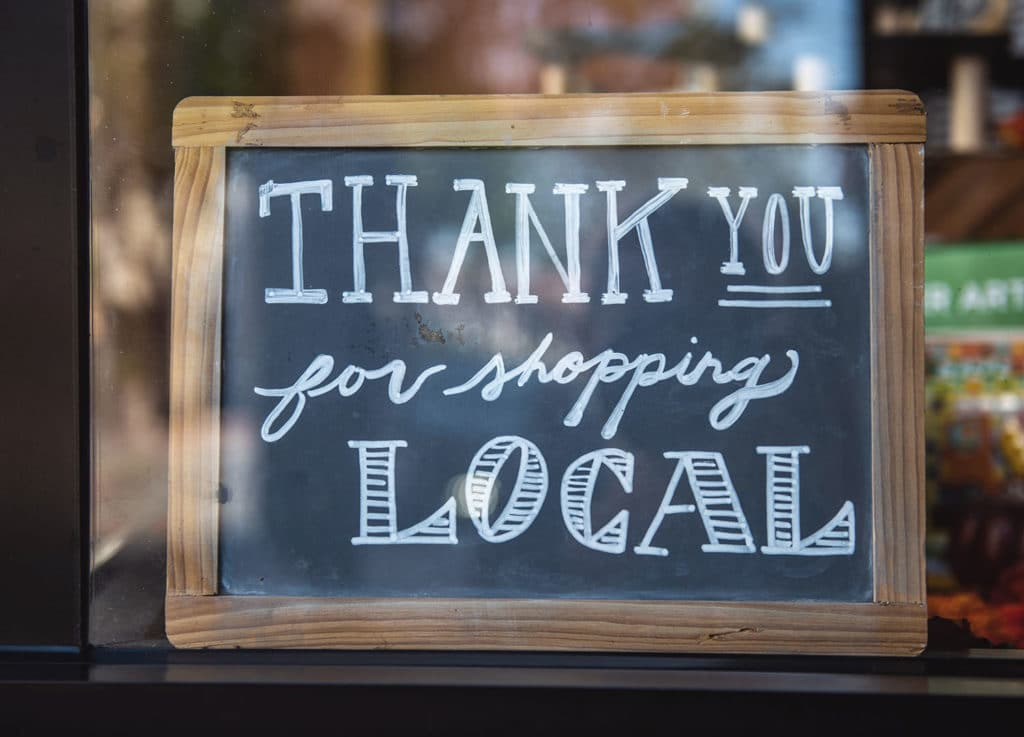 """Chalk sign in a shop window that says, """"thank you for shopping local"""""""
