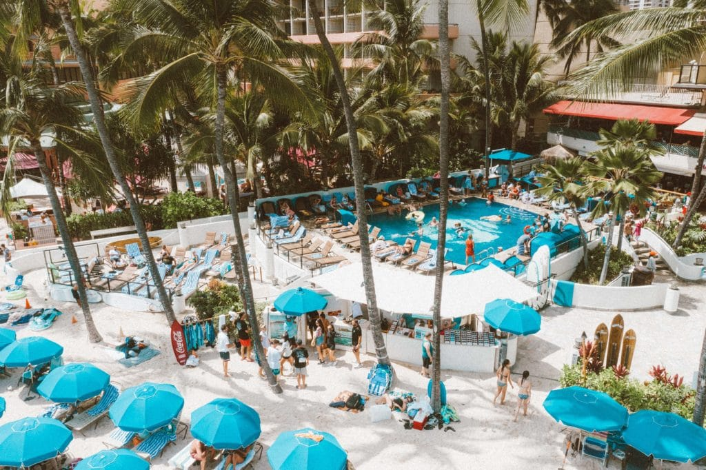Photo of hotel guests swimming in the Outrigger Hotel pool surrounded by palm trees and overlooking beach loungers under umbrellas on Waikiki Beach