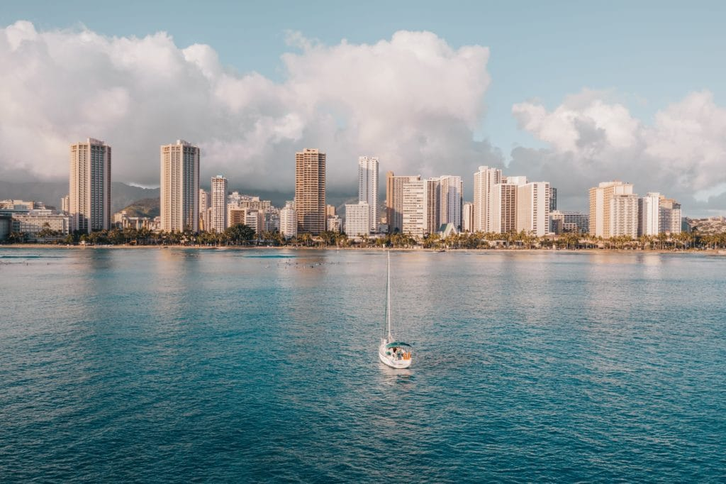 A boat floating in the Pacific Ocean off of Waikiki Beach shoreline with a skyline of buildings in the background