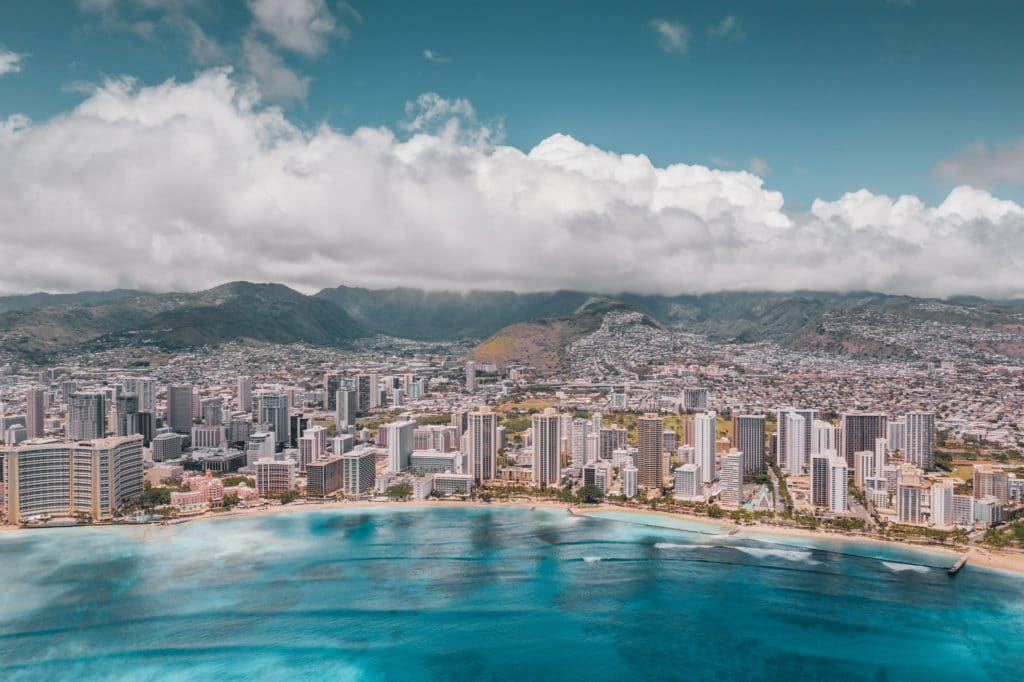 Aerial photo of Waikiki Beach. You can see rocks and coral through the bright blue water, hotels and buildings are lined behind the sand and continue off into the city. Mountains are in the background. The sky is blue with thick white clouds lingering low above the mountains.