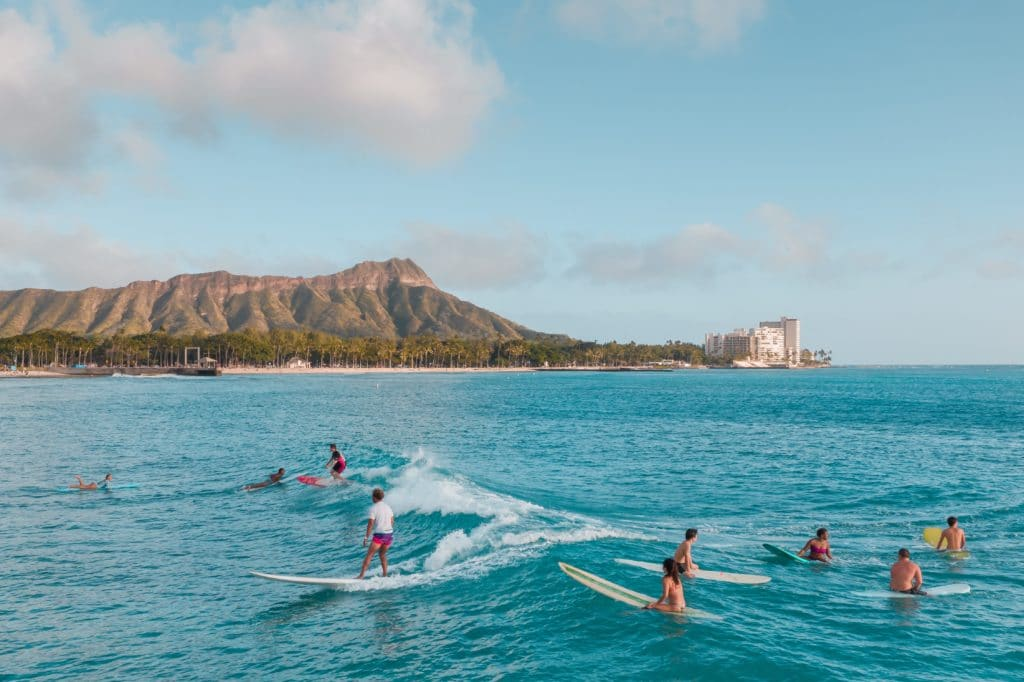 There are surfers out in the water on Waikiki Beach, catching waves on the bright blue water. Diamond Head is in the background and the sky is mostly clear with a few clouds.