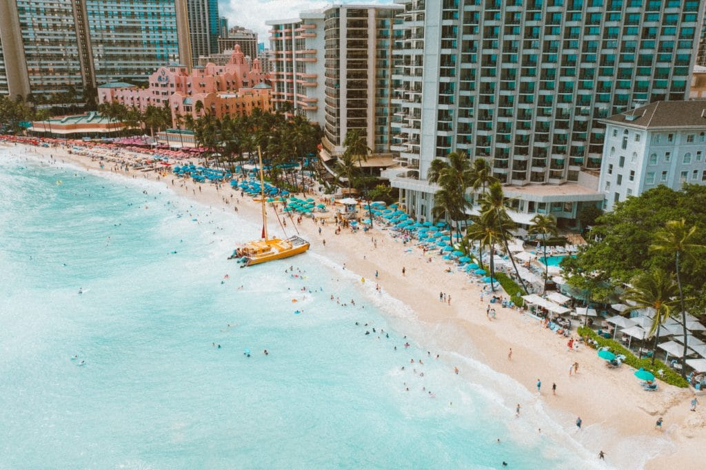 """The photo is looking down at Waikiki Beach from the water. The Royal Hawaiian """"Pink Hotel"""" stands out among the other hotels along the beach. There are bright blue beach umbrellas throughout the sand and swimmers are scattered in the ocean water. A bright yellow-orange catamaran boat is pulled up on the shore."""