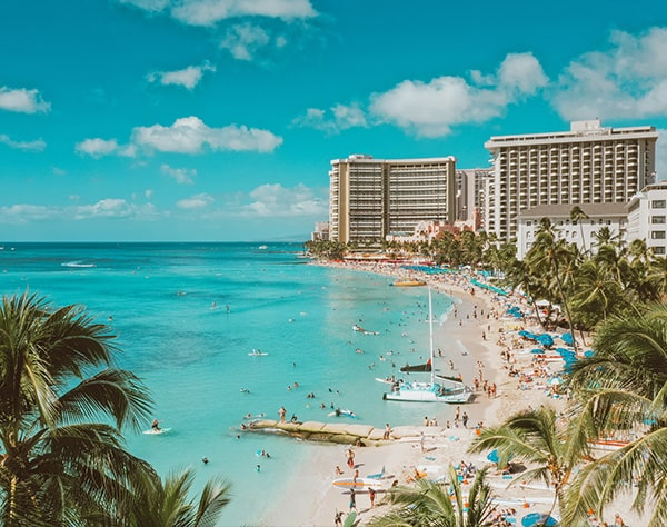 The photo is taken above the beach, looking towards the Sheraton and Royal Hawaiian Hotels. On the right, there are more hotel buildings, palms trees, and people scattered across the sand, some have blue beach umbrellas. On the left, the water is clear and blue with some surfers, stand-up paddlers, and swimmers. There are two catamaran boats docking on the shore. The sky is blue with scattered white clouds.