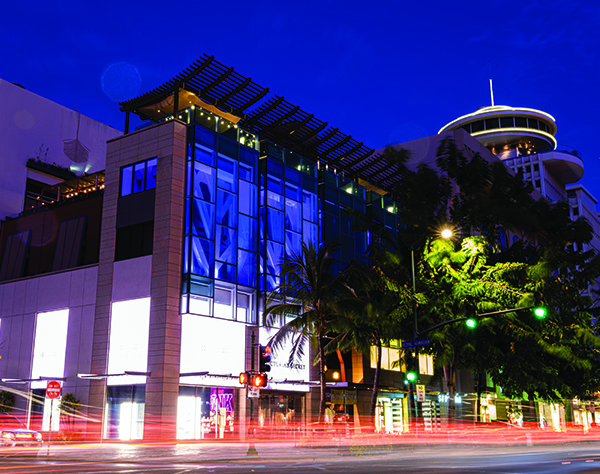 This photo was taken is night across the street of the Waikiki Shopping Plaza, looking diagonally towards the corner of the building with Victoria's Secret. Above it, there is Buho Cocina y Cantina. On the right, along the street, there are green palm trees. The photo uses a long exposure, so the streetlights and car lights look long and have a soft glow.