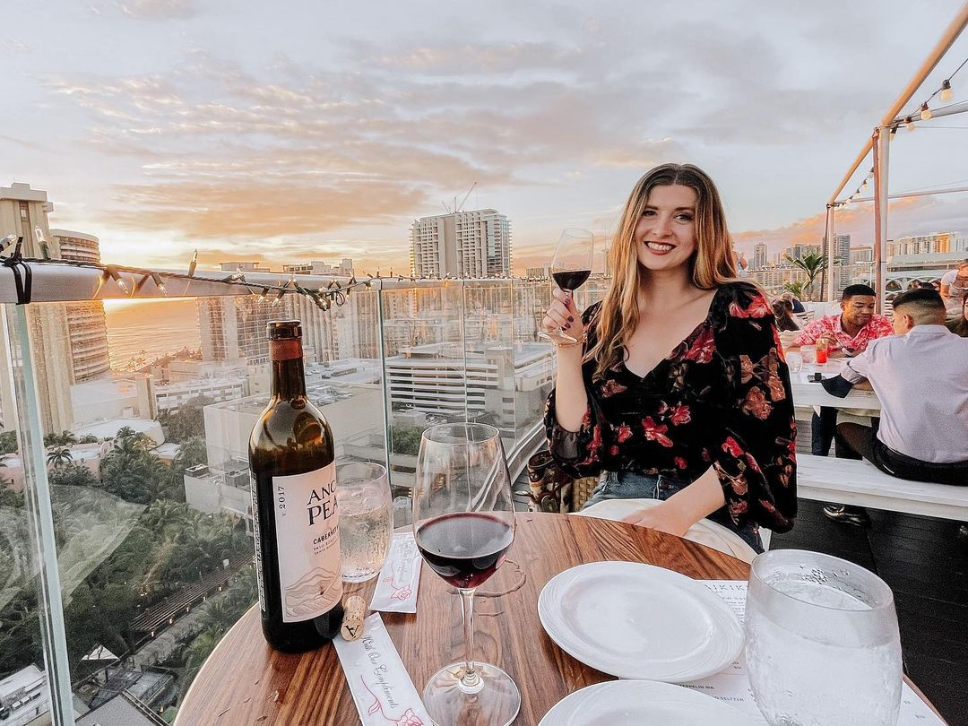 A woman holding a glass of wine at a table with a city view
