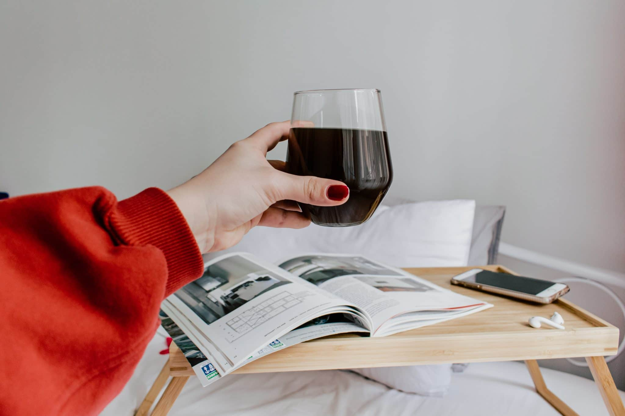 A glass of wine being held in front of a messy bed