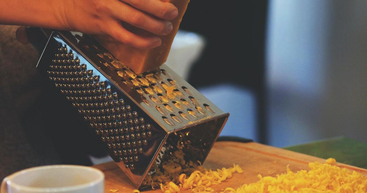 a hand shredding cheese