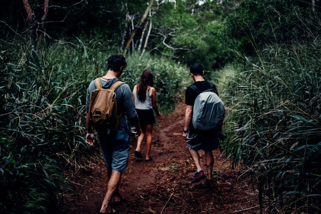group of friends hiking on a muddy trail