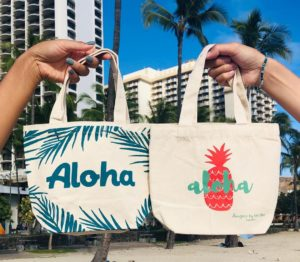 hands holding up bags with buildings and palm trees